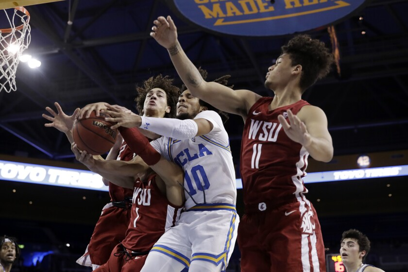 UCLA guard Tyger Campbell (10) negotiates a guard Washington State, Jervae Robinson (1) and DJ Rodman (11) for a rebound during the first half of the February 13 game at Pauley Pavilion.