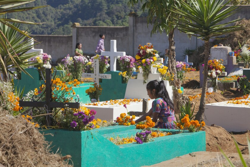 A girl places flowers on a grave during Day of the Dead activities in Guatemala.