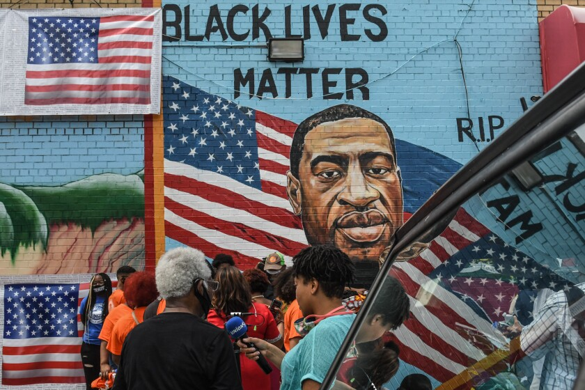 A mural painted by artist Kenny Altidor depicting George Floyd is unveiled on CTown Supermarket in  Brooklyn