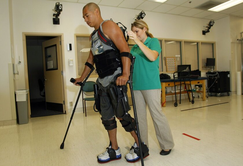 Hermes Castro walks with a help of a Ekso Bionics exoskeleton at Scripps Memorial Hospital Encinitas. Physical therapist  Alyson Cavanaugh monitors Castro and the device.