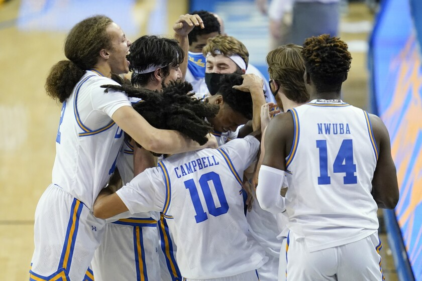 UCLA players celebrate after guard Jaylen Clark made a free throw to give the Bruins the lead.