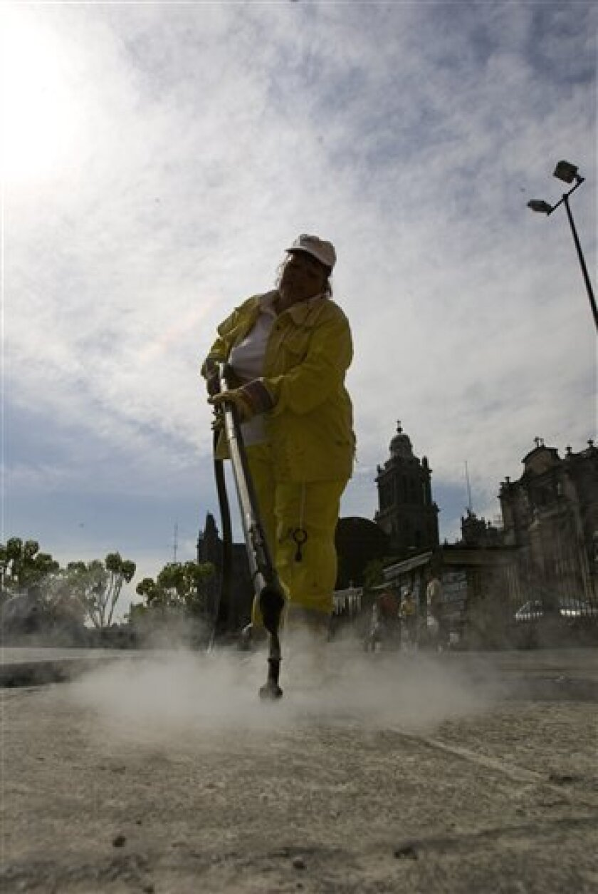 A worker using a sidewalk steam-cleaner removes chewing gum in Mexico City, Wednesday, Jan. 7, 2009. The country that gave the world chewing gum is getting gummed up; the average square yard of Mexico City sidewalk has 70 blobs of discarded chew. (AP Photo/Eduardo Verdugo)