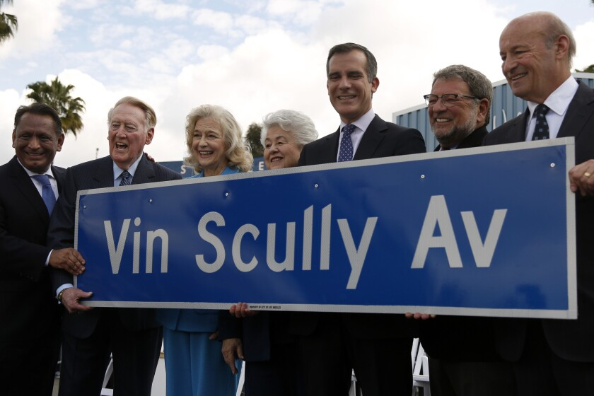 Vin Scully, second from left, holds a street sign named in his honor on Monday as the longtime Dodger broadcaster is retiring after this season.