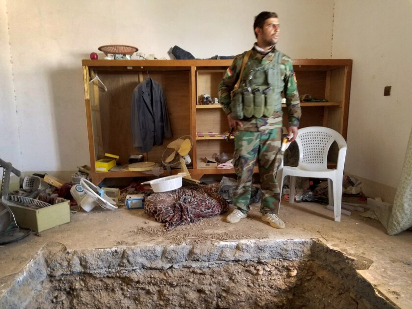 Ibrahim Hussein, 23, a peshmerga fighter, stands near a tunnel leading to the underground hide-out of an Islamic State leader reportedly killed in Shakoli, Iraq, during this week's Mosul offensive.
