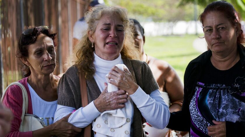Grieving relatives of passengers who perished in Cuba's worst aviation disaster leave the morgue, in