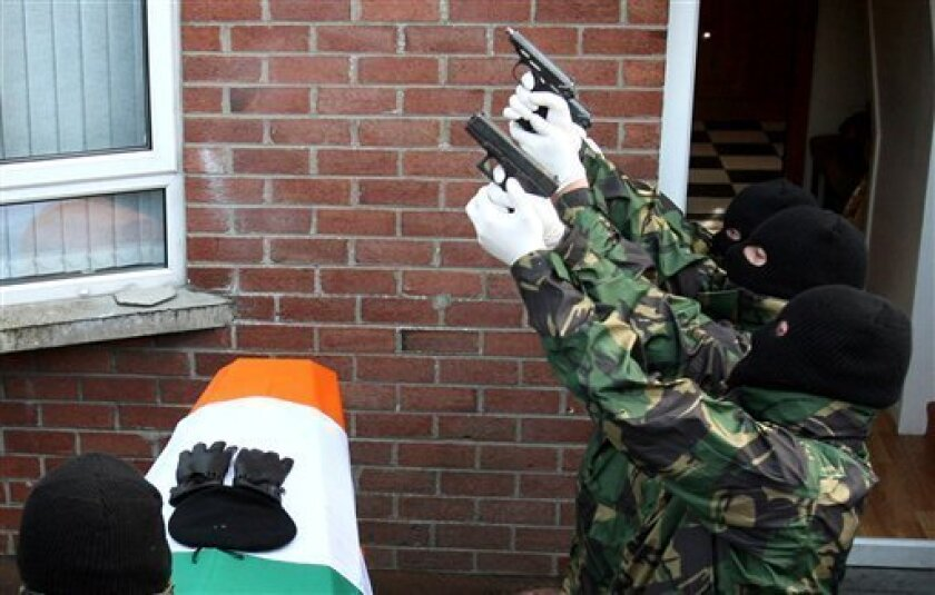 Masked gunmen fire a volley of shots over the coffin of Republican John Brady, outside his sister's home in Strabane, Northern Ireland, Thursday Oct. 8, 2009. Brady, 40, hanged himself in a police cell last Saturday after being arrested over a domestic dispute while on weekend parole from prison, and it was claimed that he could not face the prospect of returning to jail.(AP Photo/Peter Morrison)