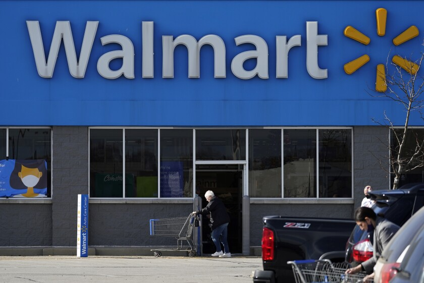 FILE - In this Nov. 5, 2020 file photo, a woman pushes a shopping cart to enter a Walmart in Rolling Meadows, Ill. Walmart turned out another stellar quarter as the world's largest retailer powers through a pandemic that has felled other national chains. The Bentonville, Arkansas-based retailer delivered a 56% increase in its fiscal third-quarter profits while revenue rose 5.3%. (AP Photo/Nam Y. Huh, File)