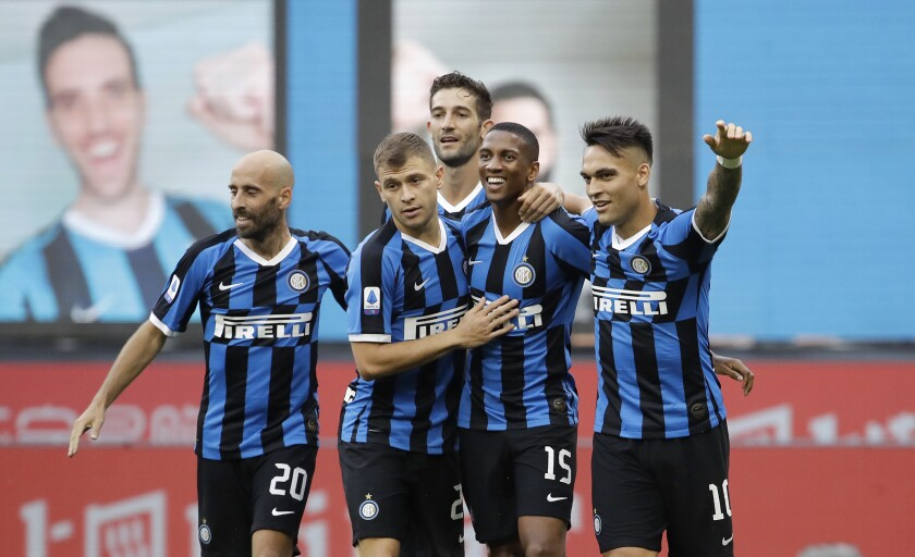 Inter Milan's Ashley Young, second from right, celebrates with his teammates after scoring his side's opening goal during the Serie A soccer match between Inter Milan and Brescia at the San Siro Stadium, in Milan, Italy, Wednesday, July 1, 2020. (AP Photo/Luca Bruno)