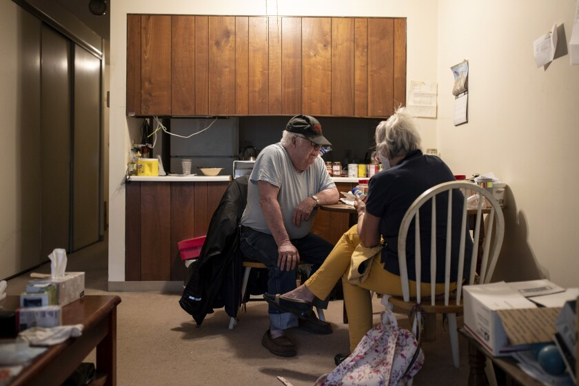 Kathleen McAuliffe, a home care worker, helps client John Gardner with his weekly chores.