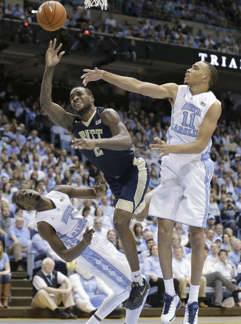 North Carolina's Brice Johnson (11) and Theo Pinson (1) defend against Pittsburgh's Michael Young (2) during the second half of an NCAA college basketball game in Chapel Hill, N.C., Sunday, Feb. 14, 2016. North Carolina won 85-64. (AP Photo/Gerry Broome)