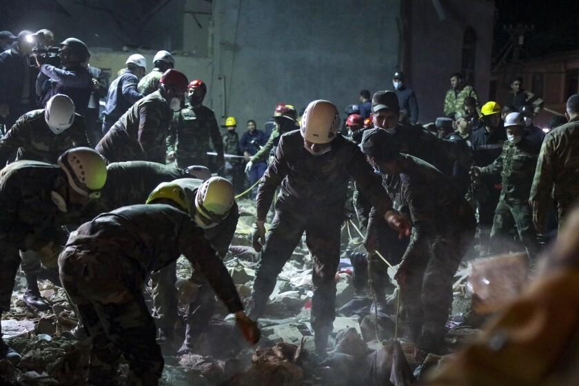 Soldados y bombertos buscan sobrevivientes en una zona residencial alcanzada por un misil armenio