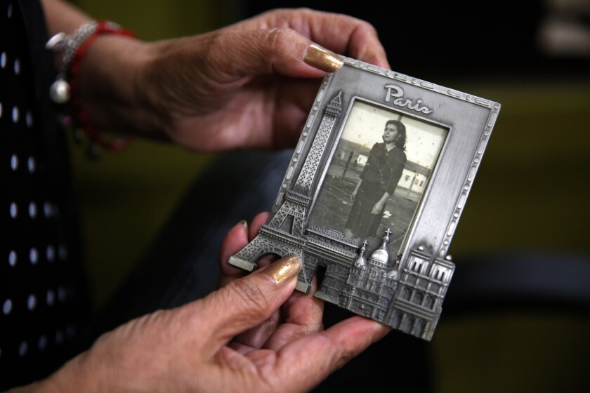 Hairstylist Virginia Guzman holds a picture of her mother, Maura Jimenez