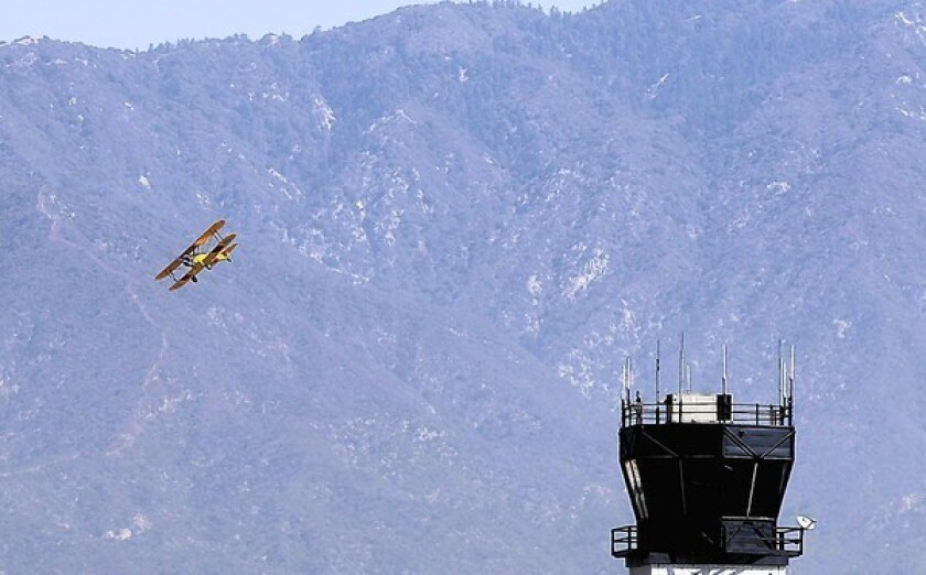 With the San Gabriel Mountains as a backdrop, aviator Gabe Lopez brings his vintage biplane in for a low pass during an open house at the El Monte Airport. Supporters of the airport fear it will be overtaken by pressure to develop the land.
