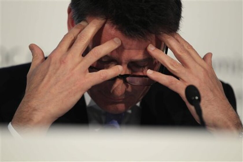 Sebastian Coe, the Chairman of the London Organizing Committee for the Olympic Games (LOCOG) holds his hands to his head during a news conference to mark the end of a visit by members of the International Olympic Committee (IOC) in London, Friday, April 1, 2011. The IOC says the Court of Arbitration for Sport has no legal jurisdiction in the British financial dispute over the 2012 London Olympics. Denis Oswald, head of the IOC coordination commission for London, says the body's own ruling in the case should be considered final. (AP Photo/Matt Dunham)