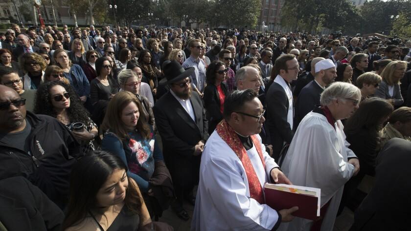 Hundreds of mourners listen to a speaker during a remembrance ceremony honoring slain USC professor Bosco Tjan.