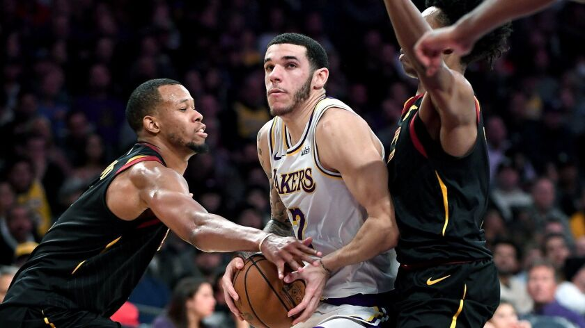 LOS ANGELES, CA. JANUARY 13, 2018-Lakers Lonzo Ball drives past Cavaliers Rodney Hood, left, and Col