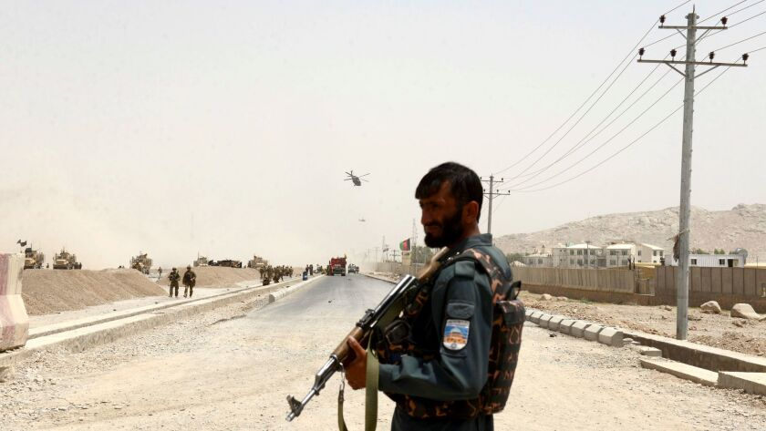An Afghan policeman stands guard in Kandahar province.