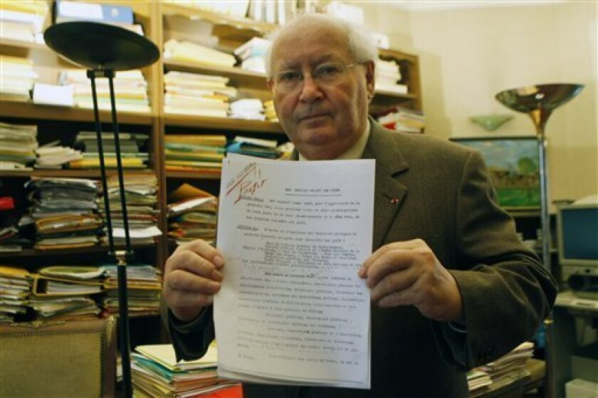 "Famed French Holocaust historian Serge Klarsfeld is photographed in his Paris office, Sunday, Oct. 3, 2010, holding a recently uncovered 1940 document. Klarsfeld said the document provides new proof of how Nazi-occupied France's wartime leader Philippe Petain ordered his government to persecute Jews. Klarsfeld says the ""important"" document includes personal notes by Petain, describing how authorities should target Jews, notably by keeping them out of public office and bar them from working in schools. Marshal Philippe Petain, who headed the 1940-1944 collaborationist Vichy regime, was found guilty of treason and imprisoned on an island off the Atlantic coast until his death in 1951. (AP Photo/Jacques Brinon)"