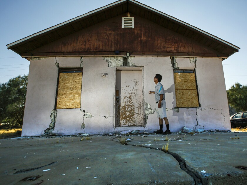 Jenner Kim, 50, of Trona examines his storage building, which was badly damaged by the July Fourth quake.