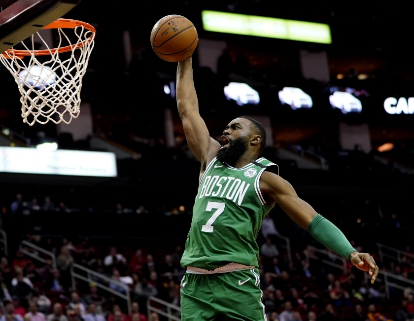 FILE - In this Feb. 11, 2020, file photo, Boston Celtics' Jaylen Brown goes up to dunk against the Houston Rockets during the second half of an NBA basketball game in Houston. Brown is encouraged by the steps the NBA is taking to connect with its players' desire to support social justice causes. He also says he wants to see the league go further with some of those plans as it prepares to restart the season later in Florida. (AP Photo/David J. Phillip, File)