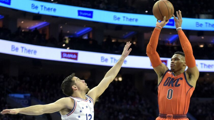 Oklahoma City Thunder's Russell Westbrook (0) takes a shot over Philadelphia 76ers' T.J. McConnell (