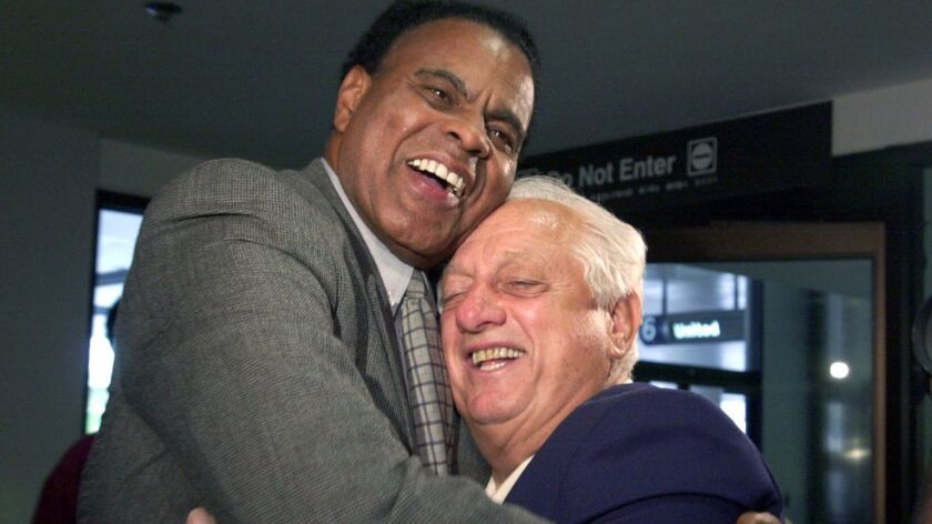 Dodgers vice president of external affairs Tommy Hawkins, left, greets former Dodgers manger Tommy L