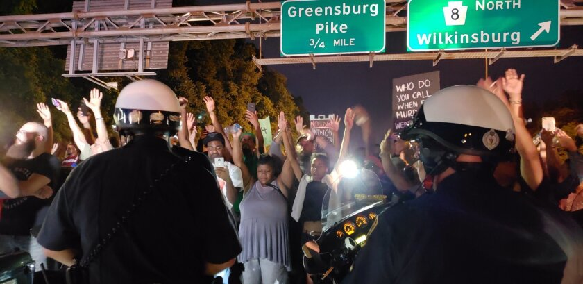 """Protesters chant """"Hands up! Don't shoot!"""" at motorcycle officers near the head of a line of vehicles stuck on Interstate 376 in Pittsburgh on June 21, 2018. The highway was shut down by the people protesting the East Pittsburgh police after the June 19 shooting death of Antwon Rose."""