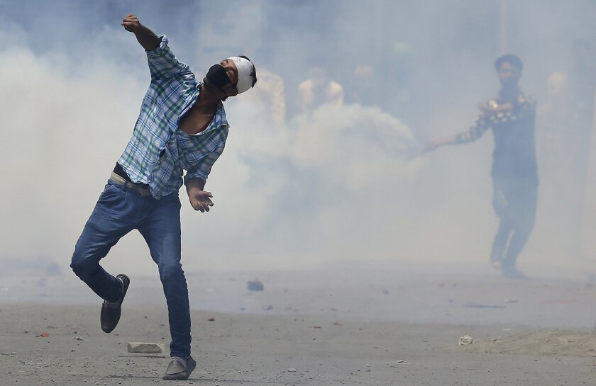 Kashmiri Muslim protesters throw stones at Indian paramilitary soldiers in Srinagar, Indian controlled Kashmir, Sunday, July 10, 2016. Indian troops and protesters clashed in several parts of the state despite a curfew imposed in the Himalayan region following the killing of a popular rebel commander. (AP Photo/Mukhtar Khan)