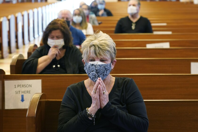 Diane Leahy prays with others before receiving the second dose of the Moderna COVID-19 vaccine at St. Patrick Catholic Church, Monday, March 1, 2021, in Miami Beach, Fla. In much of the country getting the vaccine has been tremendously difficult for many older adults. But in Miami Beach, faith leaders and the fire department have joined resources to make vaccines available to older residents. (AP Photo/Marta Lavandier)