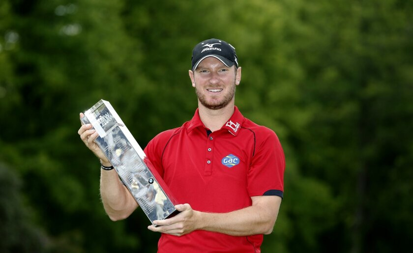 England's Chris Wood celebrates with the trophy after winning the PGA Championship at Wentworth Club, in Virginia Water, England, Sunday May 29, 2016.  Wood shot a front-nine 29 before overcoming a late run of bogeys to win the PGA Championship by one stroke for the biggest victory of his career on