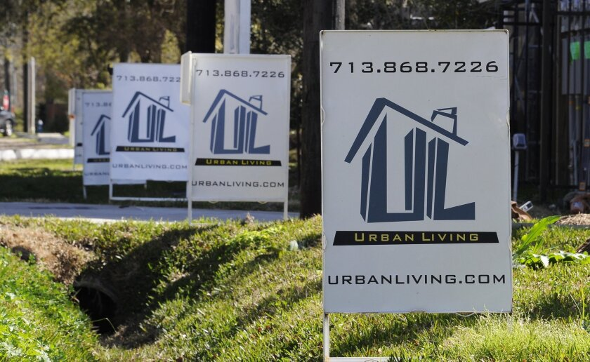 "In this Tuesday, Feb. 16, 2016, photo, ""For Sale"" signs are stacked up outside a new complex of townhouses in Houston. On Tuesday, Feb. 23, 2016, the Standard & Poor's/Case-Shiller 20-city home price index is released. (AP Photo/Pat Sullivan)"