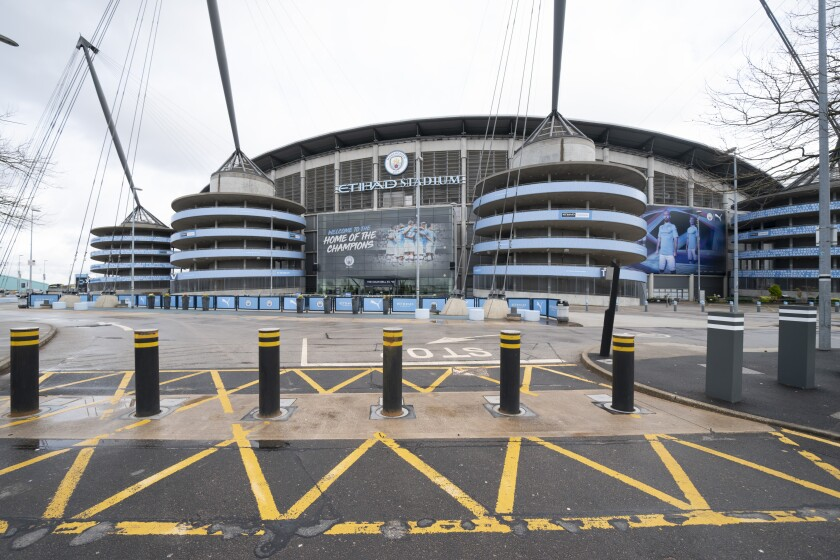 FILE - In this Saturday March 14, 2020 file photo an almost empty stadium approaches are seen around the Etihad Stadium where Manchester City was due to play Burnley in an English Premier League soccer match after all English soccer games were cancelled due to the spread of the COVID-19 Coronavirus. The Premier League resumes Wednesday June 17 after its three-month suspension because of the coronavirus outbreak. (AP Photo/Jon Super, File)