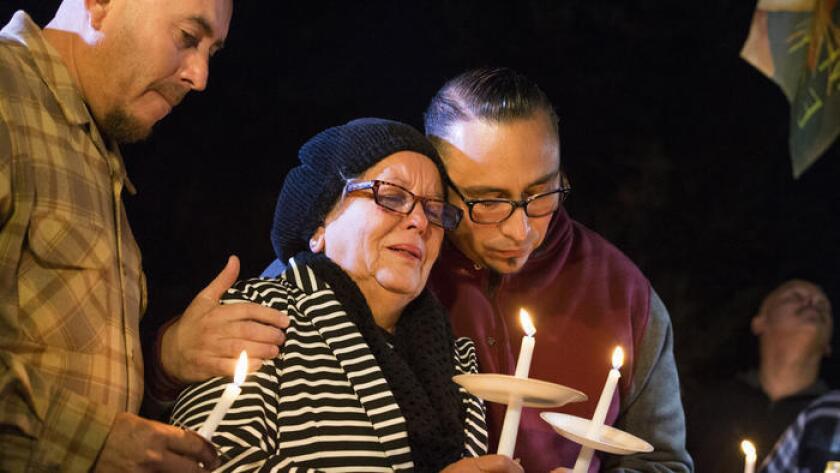 Rubia Serna es consolada por sus hijos Jesse Serna, a la derecha, y Frank Serna durante el velorio de Francisco Serna, de 73 años.