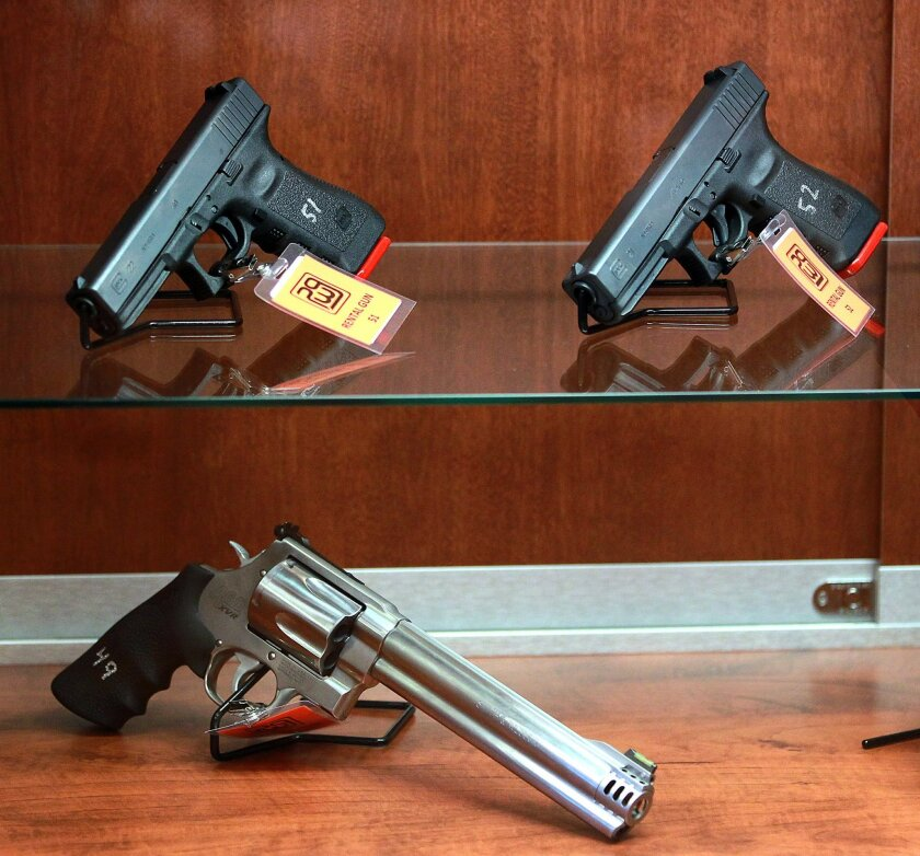 Two Glock handguns sit in a showcase atop a long-barrel revolver at Poway Weapons & Gear.
