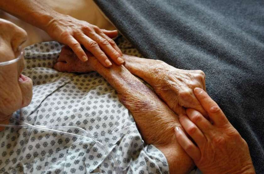 Hospice volunteers are seen caressing the hands of terminally ill patient.