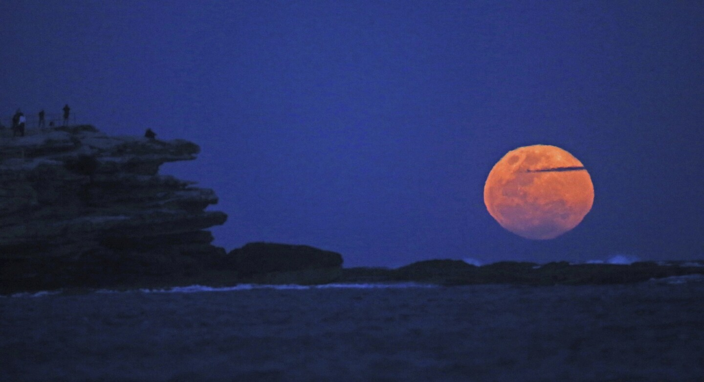 The moon rises with an orange glow as people watch from a rock cliff at Bondi Beach in Sydney. The supermoon, known to scientists as a perigee moon, occurs when Earth's neighbor appears at its largest and brightest compared with other full moons.