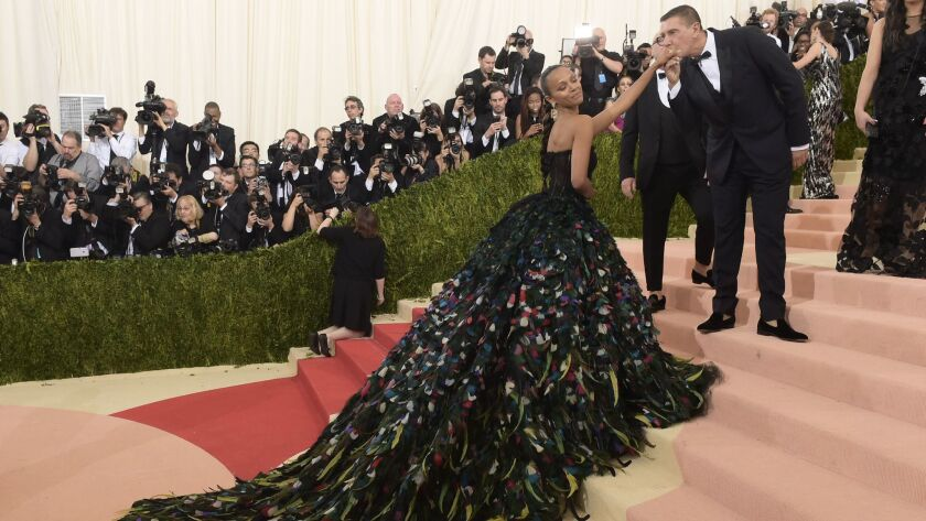 Designer Stefano Gabbana greets Zoe Saldana, in a feathered Dolce & Gabbana gown with a dramatic tra