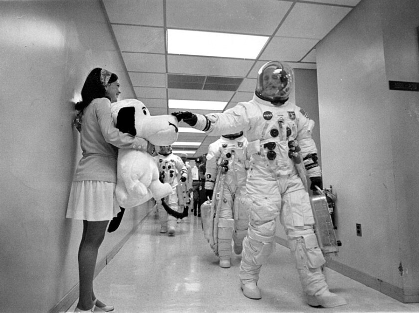 In this May 18, 1969, image obtained from NASA, Apollo 10 Commander Tom Stafford, heading to the Kennedy Space Center launch pad, pats the nose of a stuffed Snoopy held by Jamye Flowers (Coplin), astronaut Gordon Coopers secretary.