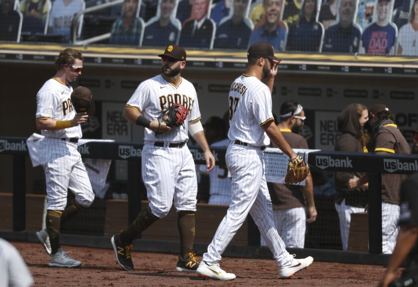 Padres pitcher Joey Lucchesi (right) and infielders Jake Cronenworth (left) and Mitch Moreland walk off after 3rd inning.