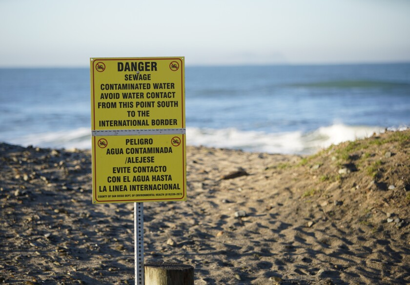 """A sign on a beach reads """"Danger - Sewage - Contaminated Water."""""""