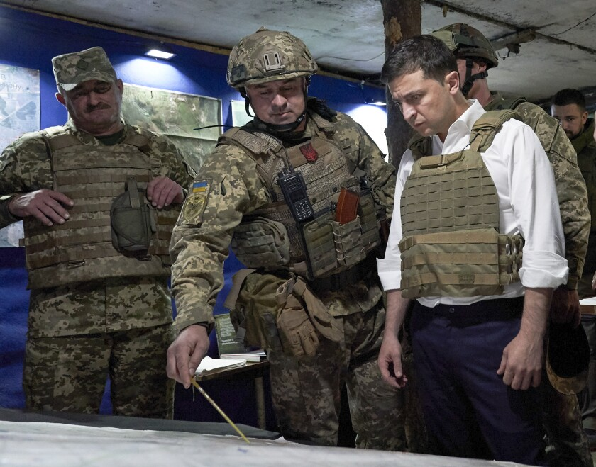 FILE - In this Oct. 14, 2019, file photo, Ukrainian President Volodymyr Zelenskiy, right, listens to a serviceman as he visits the war-hit Donetsk region, eastern Ukraine. For Zelenskiy, a summit meeting with Russia, France and Germany marks a decisive moment in his push to end more than five years of fighting with Moscow-backed separatists in the eastern part of his country. (Ukrainian Presidential Press Office via AP, File)