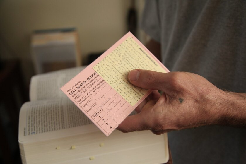 While in prison, Uriah Courtney became an avid reader and deepened his religious faith. He holds a Bible along with scraps of paper he uses to write notes, including a prison cell check receipt. David Brooks • U-T