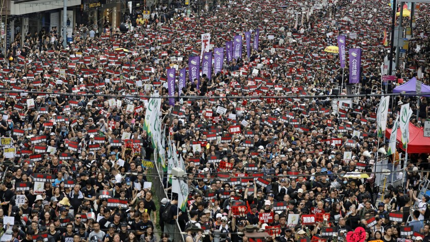 Thousands of protesters shouting slogans and carrying signs fill the streets of Hong Kong on Sunday.