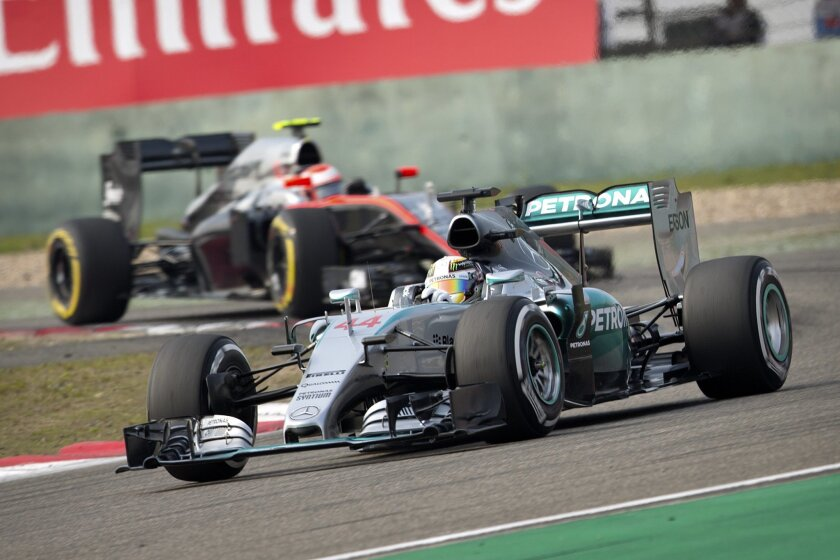 Mercedes driver Lewis Hamilton of Britain turns a corner ahead of McLaren driver Jenson Button of Britain during the qualifying session for the Chinese Formula One Grand Prix at Shanghai International Circuit in Shanghai, China, Saturday, April 11, 2015. Hamilton took pole for Sunday's race. (AP Photo/Mark Schiefelbein)