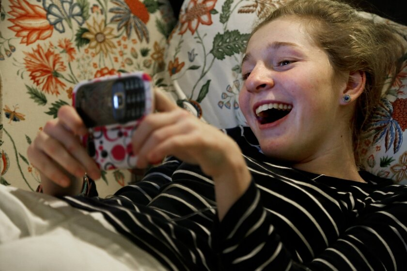 Lilly Grossman laughs with her best friend, Lindsay Crowe, while texting in her living room at home.  Grossman has been friends with Crowe since the sixth grade and the two have become inseparable.  Although Grossman's genetic disorder causes her difficulty in controlling muscle function, her brain