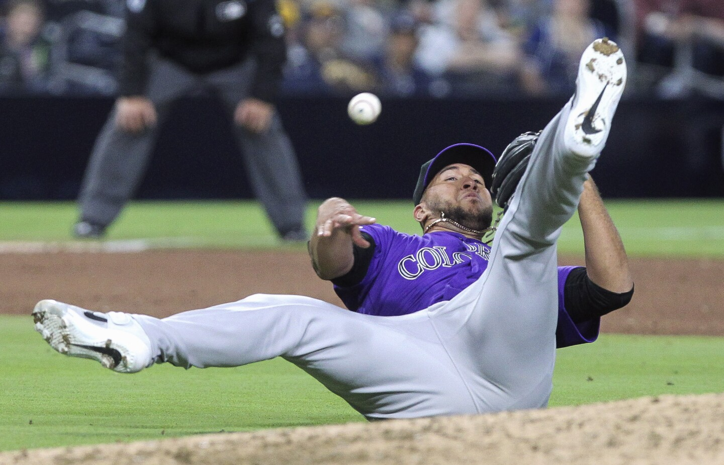 After stopping the Padres' Manuel Margot's infield hit, the Rockies' pitcher Carlos Estévez tries to throw to first base while on his back, but Estévez's throwing error allows Margot to make it to second base during the eighth inning at Petco Park in San Diego on Tuesday, April 16, 2019.