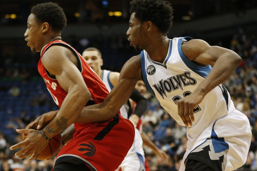 Minnesota Timberwolves forward Andrew Wiggins (22) tries to steal the ball from Toronto Raptors guard DeMar DeRozan (10) in the second half of an NBA basketball game Wednesday, Feb. 10, 2016, in Minneapolis. The Wolves won 117-112. (AP Photo/Stacy Bengs)
