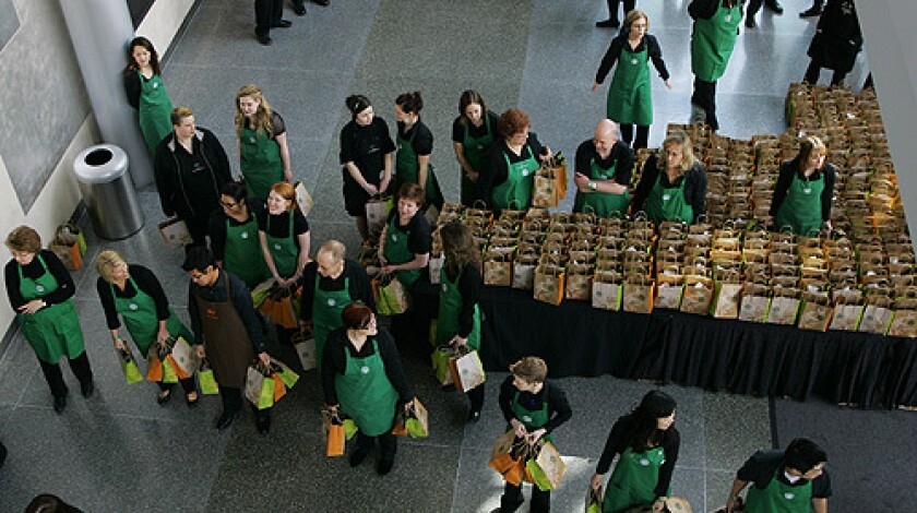 Starbucks Corp. employees wait to hand out gift bags Wednesday, March 19, 2008 at the end of Starbucks' annual shareholders meeting in Seattle.