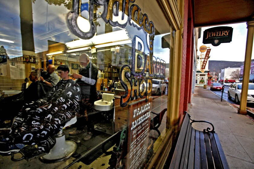 """John Lisle, right, owner of the Palace Barber Shop, cuts 14-year-old Isaiah Solus' hair in Yreka, Calif. """"I think we should do it,"""" said Isaiah about breaking away from California government."""