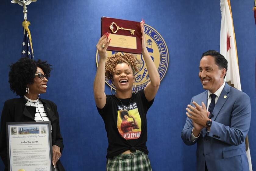 Andra Day holds up the key to the city as San Diego Mayor Todd Gloria and Councilmember Monica Montgomery Steppe look.
